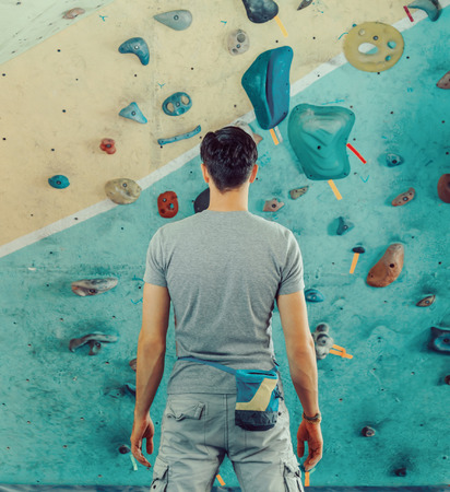 Young man standing in front of a practical climbing wall indoor and preparing to climb Stock Photo