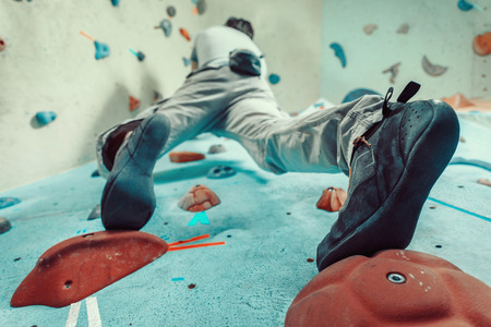 Man climbing artificial boulder indoors, view from below Stock Photo