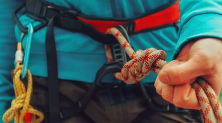 Rock climber wearing safety harness, rope and climbing equipment, close-up image