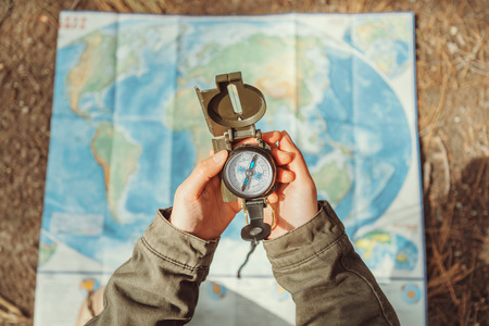 brujula: Mujer viajero en busca de dirección con una brújula en el fondo de un mapa al aire libre. Acercamiento. Punto de vista de tiro