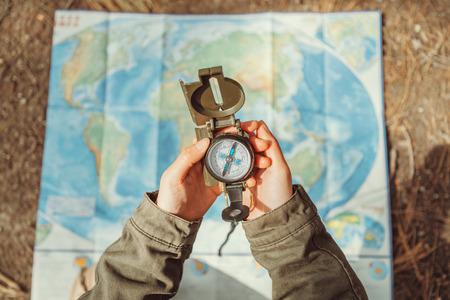 Mulher Traveler procura o sentido com um compasso no fundo do mapa ao ar livre. Fechar-se. Ponto de vista do tiro Banco de Imagens