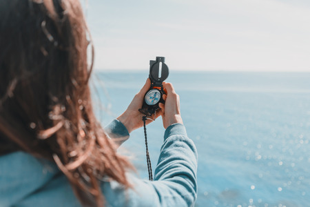 Traveler woman searching direction with a compass on coastline near the sea in summer
