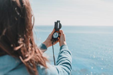 Reiziger vrouw zoekt richting met een kompas op de kust in de buurt van de zee in de zomer