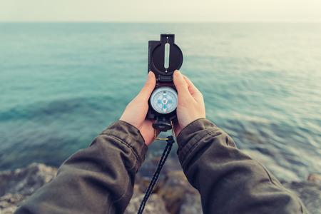 Mulher Traveler procura o sentido com um compasso no litoral de pedra perto do mar. Ponto de vista tiro.
