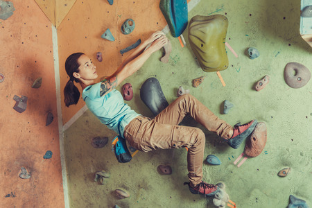magnesia: Climber sporty girl climbing on practice wall indoor