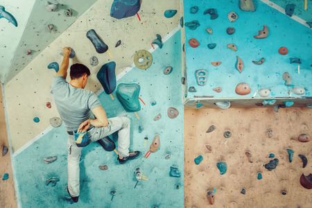 magnesia: Free climber young man coating his hand in powder chalk magnesium and climbing artificial boulder indoors