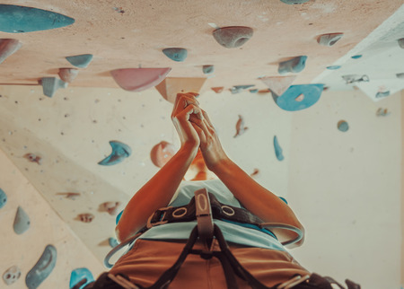 Magnesium: Climber woman coating her hands in powder chalk magnesium and preparing to climb indoor, view from below