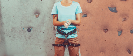 Magnesium: Climber young woman coating her hands in powder chalk magnesium and preparing to climb indoor