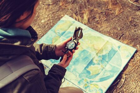 compass: Traveler young woman searching direction with a compass on background of map outdoor.