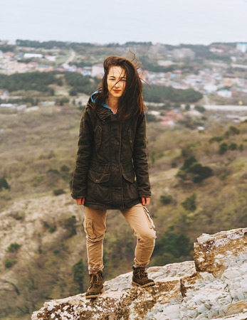 parka: Beautiful young woman dressed in parka and cargo pants standing on hill outdoor Stock Photo