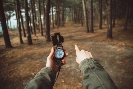 Viajante da mulher segurando uma bússola e apontando direção na floresta. Fechar-se. Ponto de vista tiro