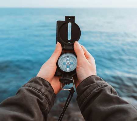 Tourist woman searching direction with a compass on stone coastline near the sea, close-up. Point of view shot. Standard-Bild