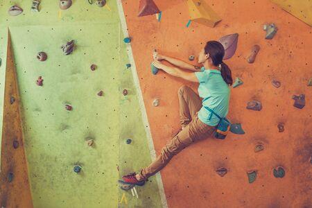 magnesia: Active climber young woman climbing artificial boulder in gym Stock Photo
