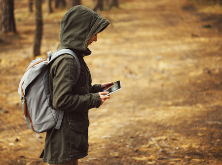 trekker: Hiker young woman looking for something on digital tablet PC in the forest
