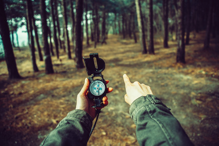 POV image of traveler woman holding a compass and pointing direction in the forest. Image with instagram color effect