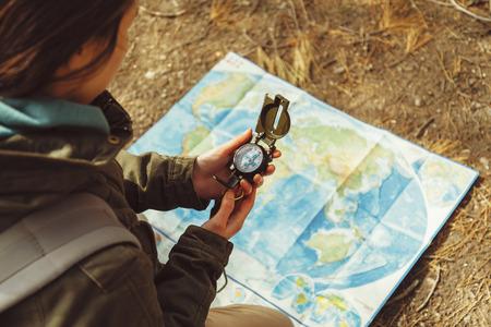 Traveler jovem mulher que procura o sentido com um compasso no fundo do mapa na floresta