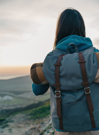 Traveler young woman with backpack walking outdoor at sunset, rear view Standard-Bild
