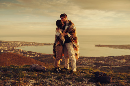 Loving couple wrapped in plaid standing on peak of mountain above bay at sunset Standard-Bild