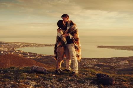 parejas de jovenes: Los pares cari�osos envueltos en tela escocesa de pie en el pico de la monta�a sobre la bah�a al atardecer