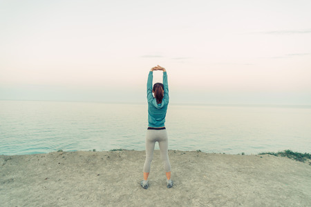 Young woman stretching her arms on coastline in summer in the morning, rear view. Concept of sport and healthy lifestyle