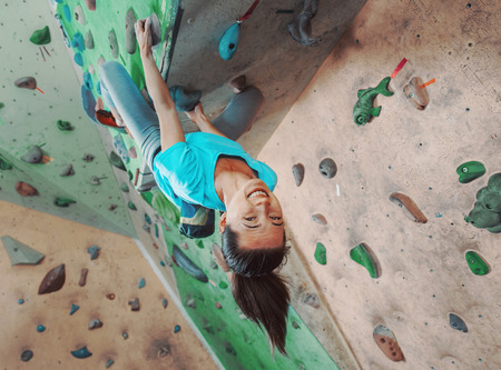 Happy young woman climbing on practical wall indoor, bouldering