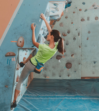 Mulher nova bonita começa a subir na parede interior prático, bouldering