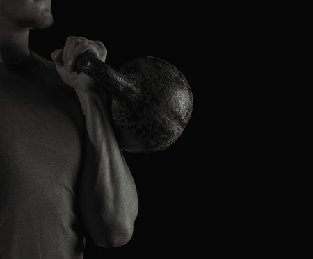 Man exercising with a kettlebell, black and white image