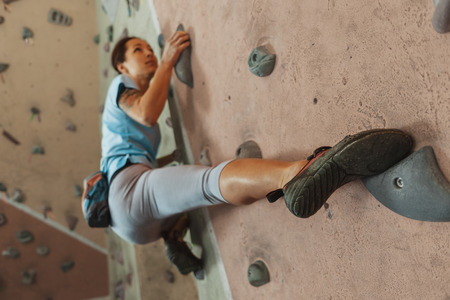 Free climber young woman climbing on practical wall indoor, bouldering Banque d'images
