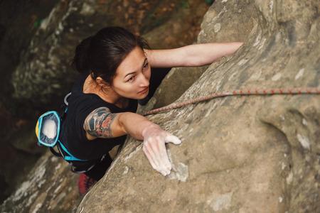 Mooie jonge vrouw klimmen op rots buiten in de zomer, bovenaanzicht Stockfoto