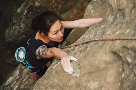 Beautiful young woman climbing on rock outdoor in summer, top view Standard-Bild