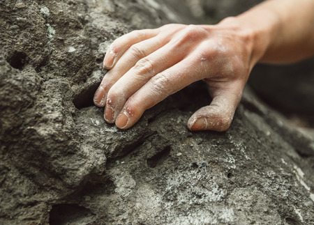 Woman climbing on rock outdoor, close-up image of climber hand in magnesium powder