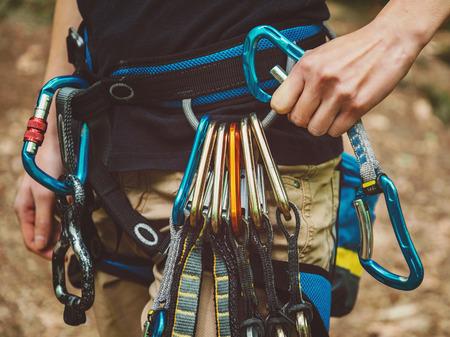 Close-up do montanhista de rocha fêmea que desgasta o cinto de segurança com quickdraws e equipamento de escalada ao ar livre