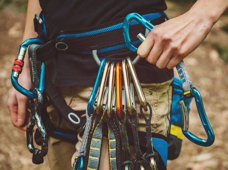 climbing sport: Close-up of female rock climber wearing safety harness with quickdraws and climbing equipment outdoor Stock Photo