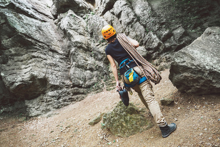 climbing sport: Young woman with climbing equipment goes to a rock outdoor, rear view Stock Photo