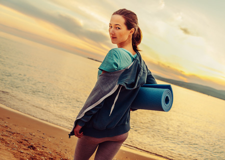 beach mat: Young beautiful woman with yoga mat standing on beach in summer at sunset and ready for workout