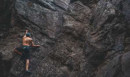 Young man climbing on stone rock outdoor