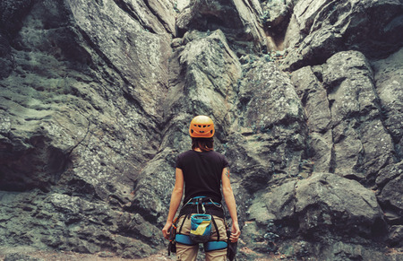 Young woman wearing in climbing equipment standing in front of a stone rock outdoor and preparing to climb, rear view 스톡 콘텐츠