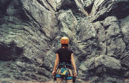 Młoda kobieta ubrana w sprzęt stoi przed kamiennej skale zewnątrz wspinaczki i przygotowuje się wspinać, widok z tyłu