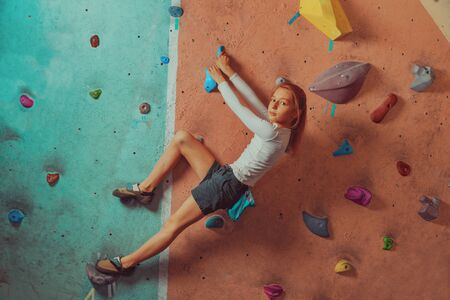 rock climb: Sporty little girl climbing artificial boulder on practical wall in gym, concept of healthy lifestyle