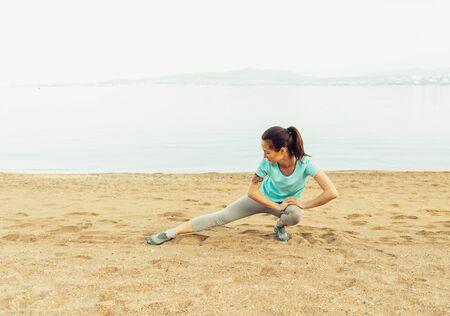 vida sana: Mujer joven que estira sus piernas y se prepara para correr en la playa cerca del mar en verano. Concepto de estilo de vida saludable