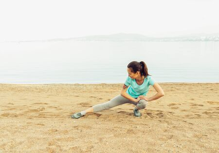 healthy person: Young woman stretching her legs and preparing to run on beach near the sea in summer. Concept of healthy lifestyle