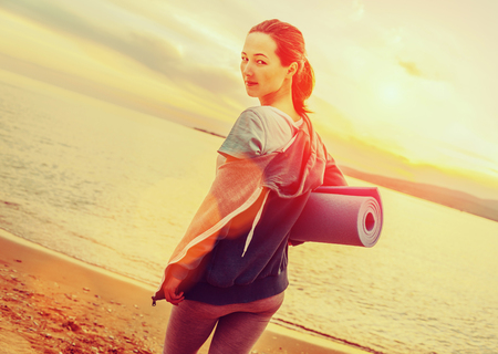 mat: Young beautiful woman with yoga mat standing on beach in summer at sunset and ready for workout. Image with sunlight effect
