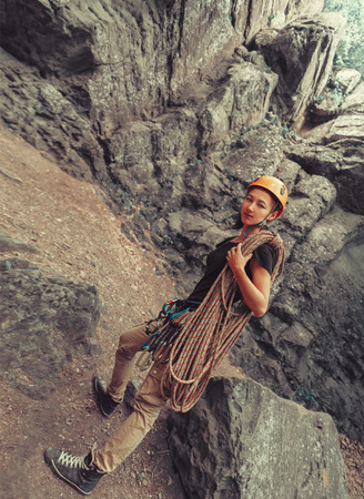 belaying: Smiling climber young woman with equipment standing in front of a stone rock outdoor and preparing to climb