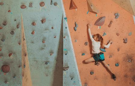 niño trepando: Deportivo niña de escalada roca artificial en la pared de práctica en el gimnasio Foto de archivo