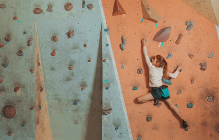 indoor: Sporty little girl climbing artificial boulder on practical wall in gym