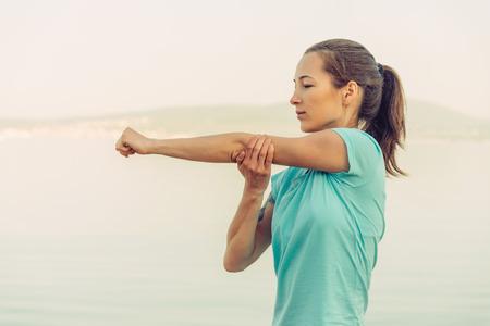 stile di vita: Giovane donna che allunga le sue braccia sulla spiaggia in estate al mattino. Concetto di stile di vita sano