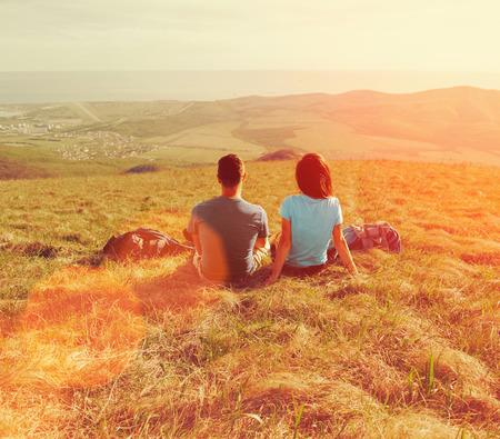 부부 산 초원에 앉아 여름 화창한 날에 자연의 전망을 즐기는 사랑
