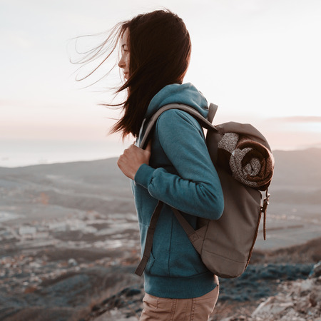 Hiker young woman with backpack standing on peak of mountain and looking into the distance in summer at sunset Stock Photo