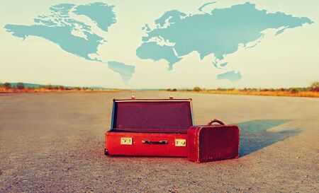 way: Vintage open suitcase and small bag on road outdoor. Map of world in the sky. Theme of travel Stock Photo