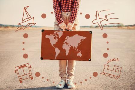 maleta: Mujer turística que sostiene una maleta con mapa al aire libre. Tipos de transporte alrededor de la oferta turística